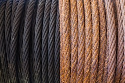 A rusty steel cable wound on a winch next to a greased new cable.