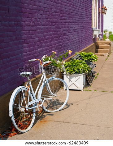A rusty vintage bicycle, painted white to hide the rust, parked along a purple brick building on the sidewalk in the springtime.