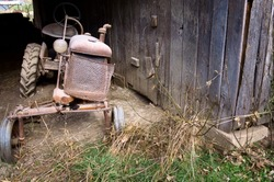 A rusty vintage tractor lies in disrepair in an abandoned country barn.