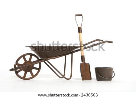 A rusty wheelbarrow, shovel and pail over white