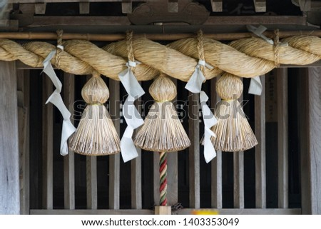 A sacred rice straw festoon and zigzag-shaped paper streamer are hang in front of Hall of worship in Shrine in Japan. #1403353049