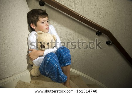 A sad and depressed boy is sitting in the corner of a staircase