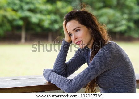 A sad and depressed woman sitting down alone outdoors