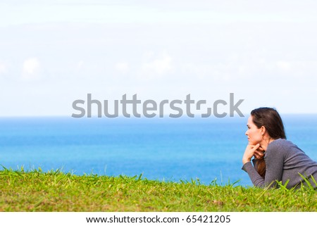 A sad and depressed young woman lying in the green grass looking sadly at  the ocean