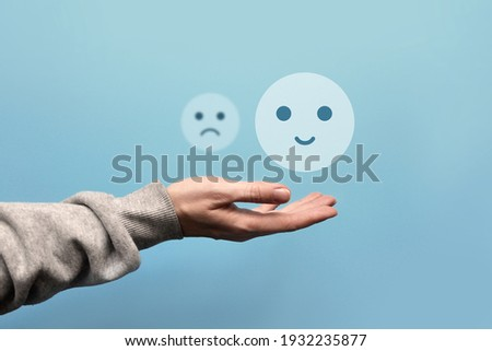 A sad and joyful face in the hand of a man. Choosing between the negative and the positive in a person's life