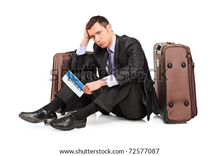 A sad business traveler seated next to a suitcase with a ticket in his hand isolated on white background - stock photo