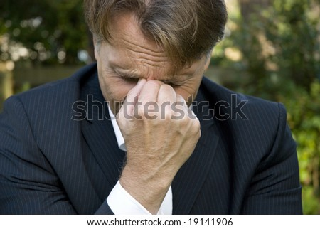 a sad businessman begins crying after hearing bad news