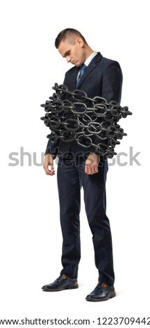 A sad businessman stands on a white background while bound by a large metal chain. Business restrictions. Loss of freedom. Chained and bound.