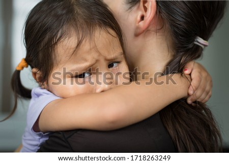 A sad child holding her mother for comfort and safety.  Foto stock ©