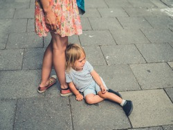 A sad crying toddler is sitting in the street by his mother's feet