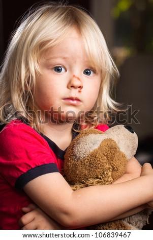 A sad cute injured boy holding a stuffed toy dog