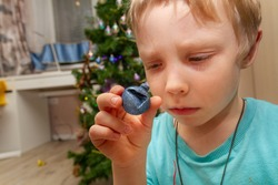 A sad little European boy looks at a spoiled bad blue ball for the Christmas tree. Preparing for the New year, decorating the Christmas tree.