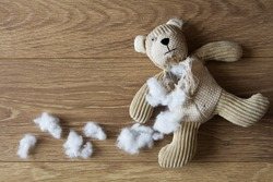 A sad looking teddy bear with his stuffing pulled out and scattered over a wooden floor.