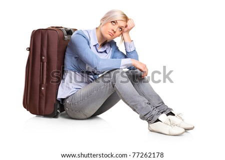A sad tourist girl seated next to a suitcase isolated on white background
