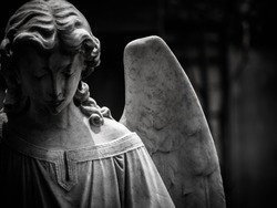 A sad winged angel at an old cemetery. Photo is in black and white with blurry effect