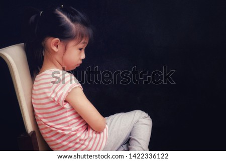A sad young Asian girl, sitting on a chair, abused, frightened and alone with dark background.  Human Rights Day. No Violence against children day. #1422336122