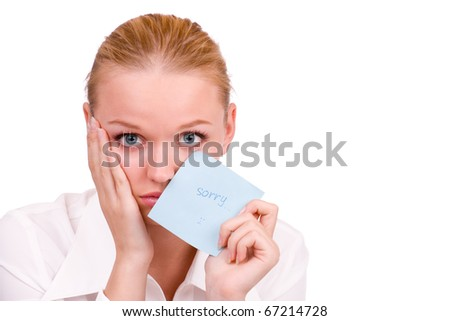 "a sad young woman holding a note saying ""sorry"""