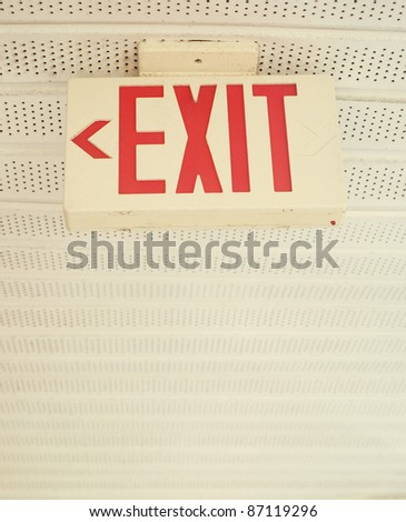 A safety exit sign with arrow pointing left.