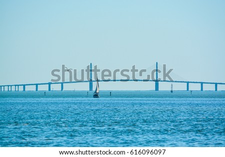 A sail boat on Tampa Bay sailing to the distant Sunshine Skyway Bridge and the Gulf of Mexico #616096097