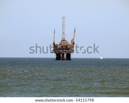 A sail boat passes a large offshore oil rig.