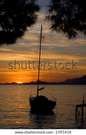 A sailboat during an orange sunset.