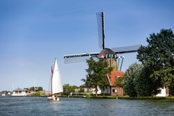A sailboat in front of the Zwanburgermill on the Warmonderleede in the Netherlands.