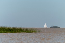 A sailboat near the horizon sailing at La Plata River in front of Colonia del Sacramento