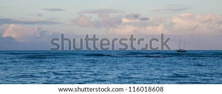 A sailboat off the coast of Waikiki beach in the early morning light. Oahu, Hawaii.
