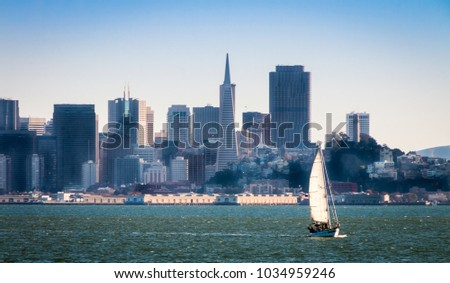 A sailboat on the San Francisco Bay sails in front of a very hazy city skyline late in the afternoon. There is green choppy water and a blue sky