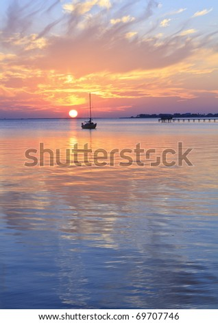 A sailboat silhouetted against a brilliant sunset in a cove off Pensacola Bay, Florida