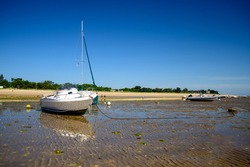 a sailing boat and a motorboat laying on the beach of plage de la Loge at Portes-en-Ré at lowtide on a sunny summertime on the Isle of île de re in the Charente-Maritime in France