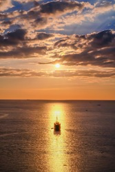 A sailing boat towards the sun, aligned with the sun reflection on water during a slightly cloudy sunset