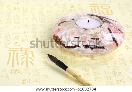A sakura candle-holder with a calligraphy brush against the Chinese characters on yellow paper