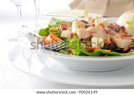 A salad with blue cheese, chicken, bacon, walnuts and dried cherries