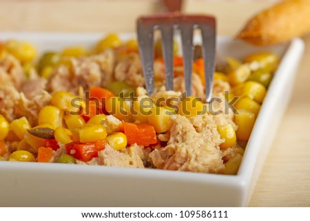 A salad with corn, carrots and tuna in a white square plate