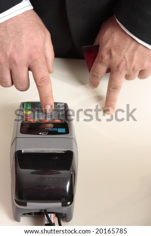 A saleasman inputs details or customer inputting a  pin number for a credit card or debit card transaction