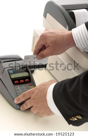 A salesman retailer swipes a credit or debit card through a pos terminal.  Focus to terminal and card.  Details removed from card.