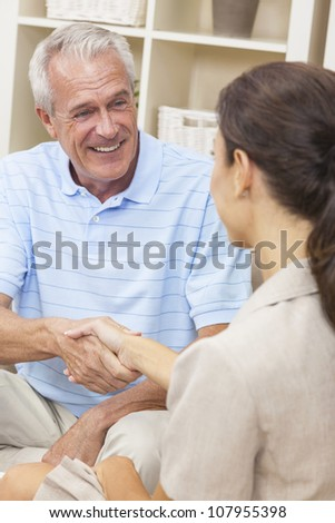 A saleswoman shaking hands with a senior man at home