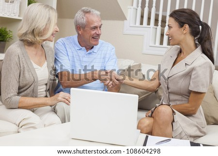A saleswoman with laptop computer shaking hands with a senior couple at home