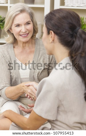 A saleswoman with shaking hands with a senior woman at home