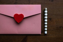A salmon coloured envelope holding a wedding invitation with a red felt heart as the seal, next to a small gold and white pen on a dark wooden desk, Toronto, Ontario, Canada.