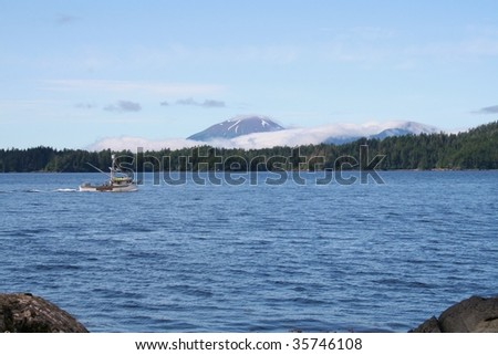 A salmon fishing boat passes in front of Sitka Alaska's Mt. Edgecumbe volcano