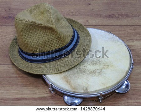 A samba player (sambista) hat and a pandeiro (tambourine), a Brazilian percussion musical instrument. The instrument is widely used to accompany samba and choro, two popular Brazilian rhythms.