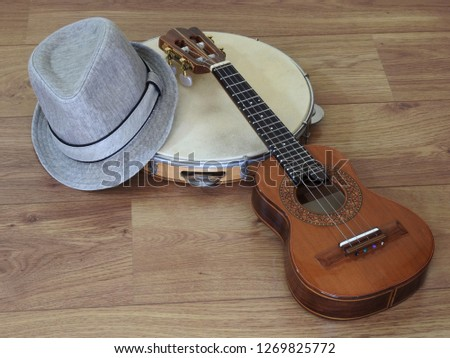 A samba player (sambista) hat and two Brazilian musical instruments: cavaquinho and pandeiro (tambourine). The instruments are widely used to accompany samba and choro, two popular Brazilian rhythms.