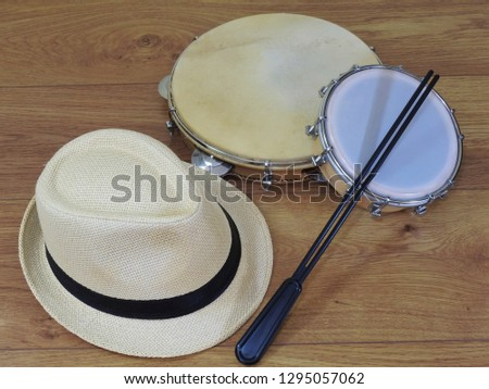 A samba player (sambista) hat and two Brazilian percussion musical instruments: pandeiro (tambourine) and tamborim with drumstick. The instruments are widely used to accompany samba music.