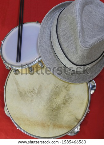 """A samba player (sambista) hat and two Brazilian percussion musical instruments: """"tamborim"""" with drumstick  and pandeiro (tambourine). The instruments are widely used to accompany samba music."""