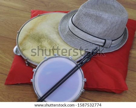 """A samba player (sambista) hat and two Brazilian percussion musical instruments: """"tamborim"""" with drumstick  and """"pandeiro"""" (tambourine). The instruments are widely used to accompany samba music."""