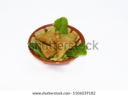 A samosa (/səˈmoʊsə/) is a fried or baked dish with a savoury filling, such as spiced potatoes, onions, peas, meat, or lentils