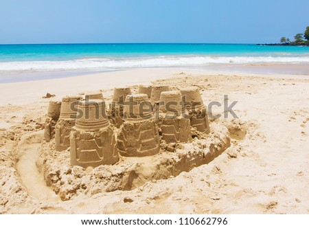 A sand castle at the beach against blue sky and crystal blue water