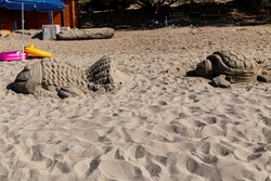 a sand sculpture of a turtle and a big fish made of sand on the beach.